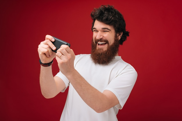 Photo of excited bearded man dressed in tshirt playing at phone over red wall