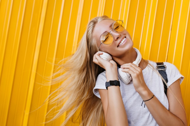 Photo of excited blonde girl in sunglasses posing on yellow background with hair waving.