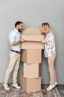 Photo of excited caucasian couple in casual clothing opening cardboard box isolated