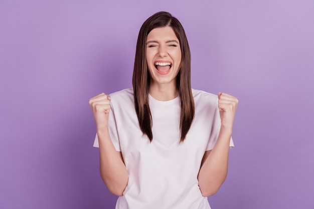 Photo of excited ecstatic girl with raised fists isolated on purple background