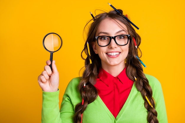 Photo of excited girl pencil haircut hold magnifying glass wear shirt isolated yellow color background