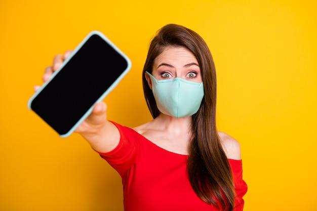 写真興奮した女の子ショースマートフォン新しい現代技術のプロモーションcovid検疫ソリューション着用赤いトップスタイルスタイリッシュなトレンディな医療マスク分離された明るい輝き色の背景