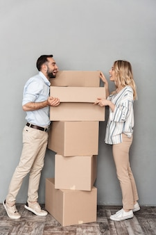 Photo of excited laughing couple in casual clothing opening cardboard box isolated