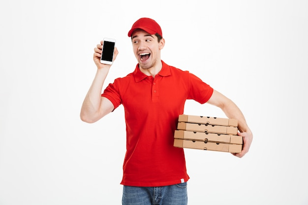 Photo of excited man 25y from delivery service in red t-shirt and cap holding stack of pizza boxes and showing mobile phone, isolated over white space