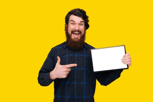Photo of excited man with beard pointing at white screen of tablet, standing over yellow wall