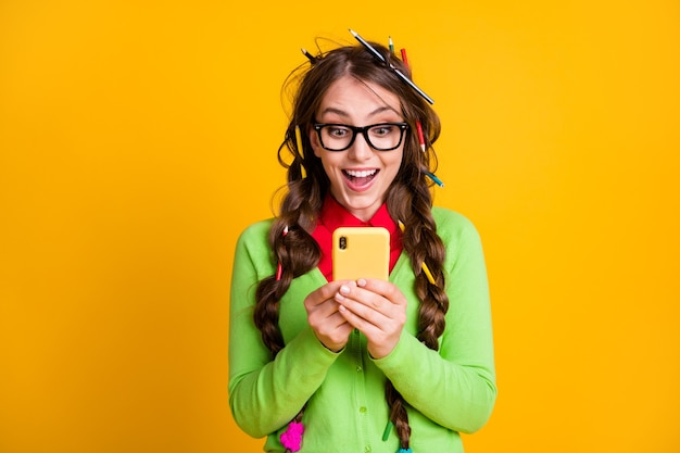 Photo of excited nerd girl read college exam news smartphone isolated yellow color background