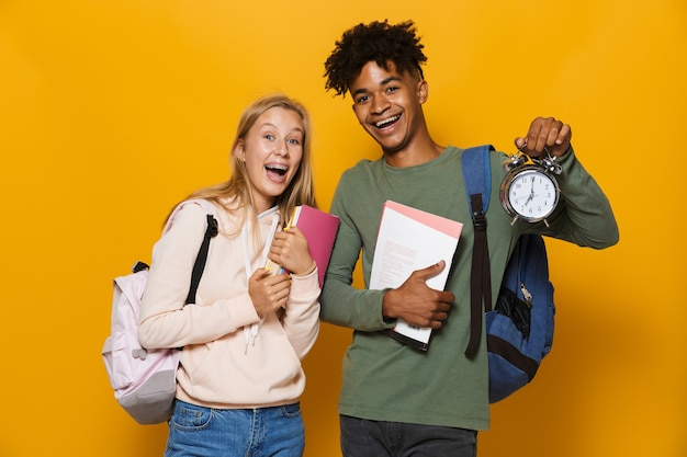 Photo of excited students man and woman 16-18 wearing backpacks holding exercise books and alarm clock, isolated over yellow background