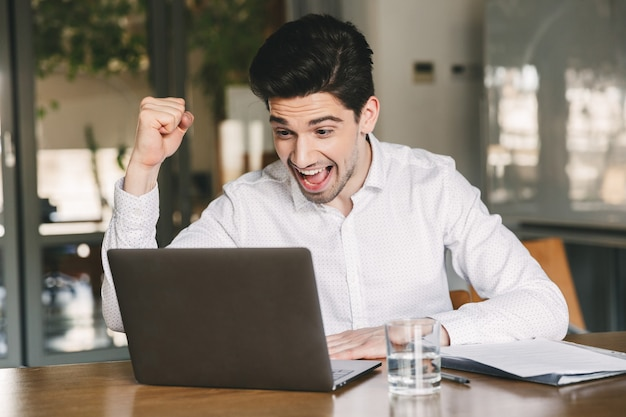 Photo of excited young man 30s wearing white shirt and bluetooth earbuds screaming and clenching fist like winner, while looking at laptop in office