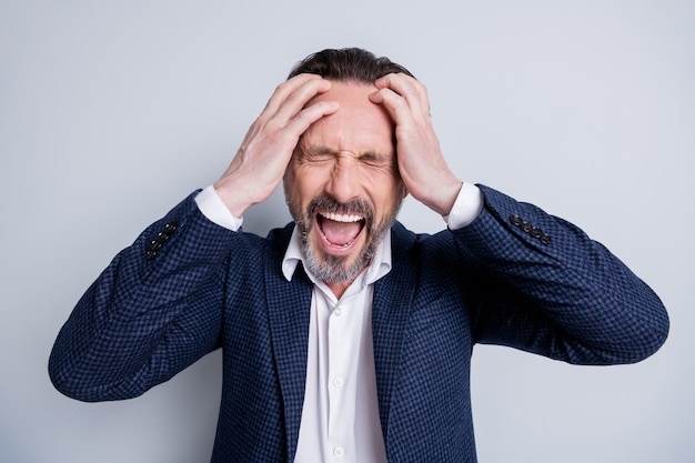Photo of exhausted stressed worker aged mature guy manager agent lost job hopeless financial crisis crash hold arms on head yelling loud despair wear suit isolated grey background