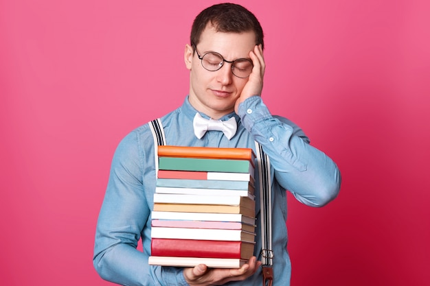 Photo of exuasted handsome student, holding huge stack of books, suffers from terrible headache, posing with hand on temple