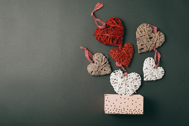 Photo of falling red and white craft hearts from gift box with copyspace for text