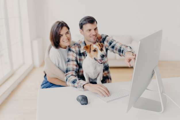 Photo of family couple make shopping on favourite website, enjoy time together, funny dog focused in monitor of computer, sits in coworking space.