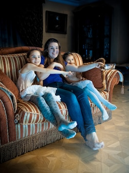 Photo of family with kids watching tv at late evening
