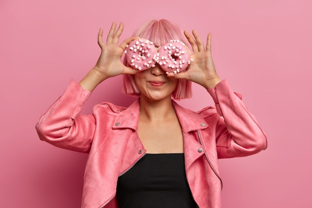 Photo of fashionable pink haired asian girl covers eyes with delicious donuts, enjoys aromatic tasty confectionery, eats glazed doughnuts