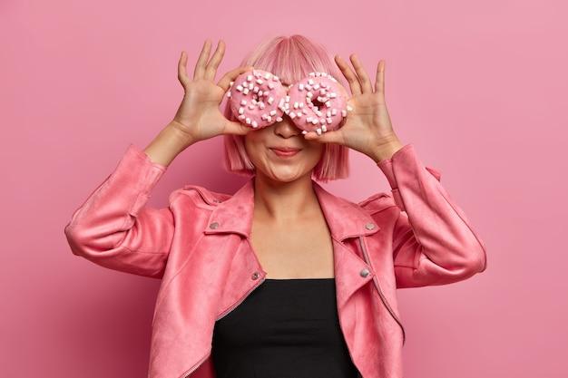 La foto della ragazza asiatica dai capelli rosa alla moda copre gli occhi con deliziose ciambelle, gode di gustosi dolciumi aromatici, mangia ciambelle glassate