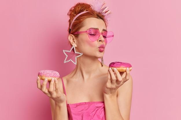 Foto di donna europea glamour rossa alla moda tiene le labbra piegate tiene due ciambelle appetitose vuole mangiare dessert dolce