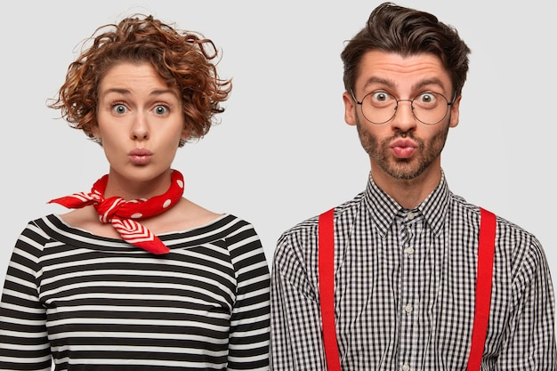 Photo of fashionable woman and man pout lips, gaze with surprised intrigued expressions, stand shoulder to shoulder, model against white wall. people, emotions, style and clothes concept