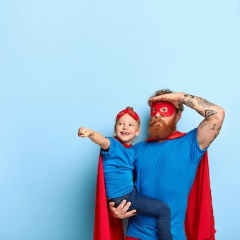 Photo of father and daughter play together, wear superhero costumes