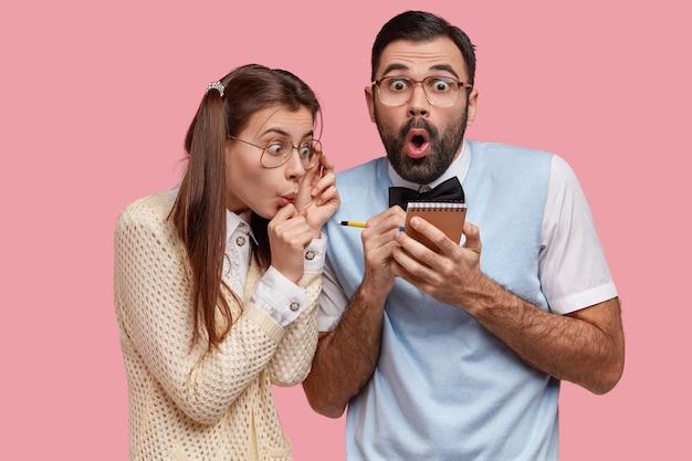 Foto di paurose femmine e maschi nerd annotare le note nel blocco note a spirale, fare dischi, sorpresi con l'elenco da fare
