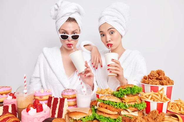Photo of female best friends drink soda have diet breakdown unhealthy nutrition delicious fast food