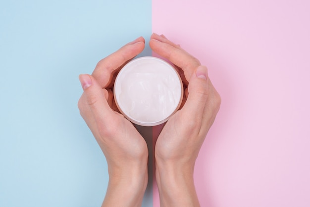 Photo of female hands and cream bottle bicolor blue and pink