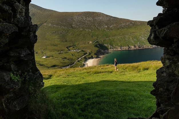 Photo of female traveler in keem bay achill island ireland through a window of an old building