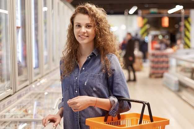 Photo of female with curly hair and attractive look, holds shooping cart, buys products in supermarket, searches for necessary products in grocery.