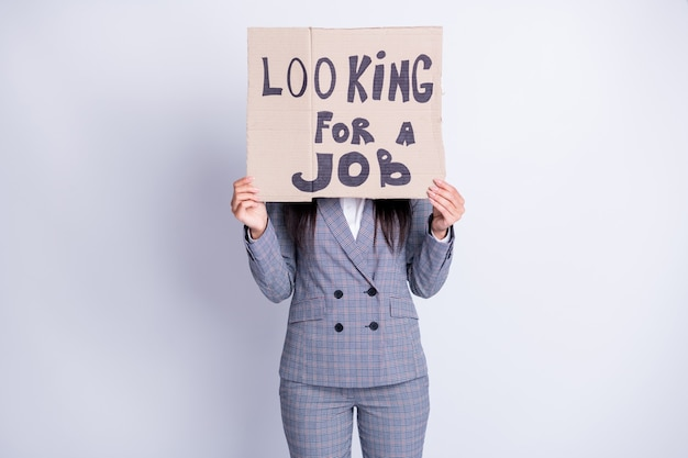 Photo of fired lady hold carton placard seek job hiding sad upset face stressed need money for living have two children search any offer formalwear plaid suit isolated grey color background