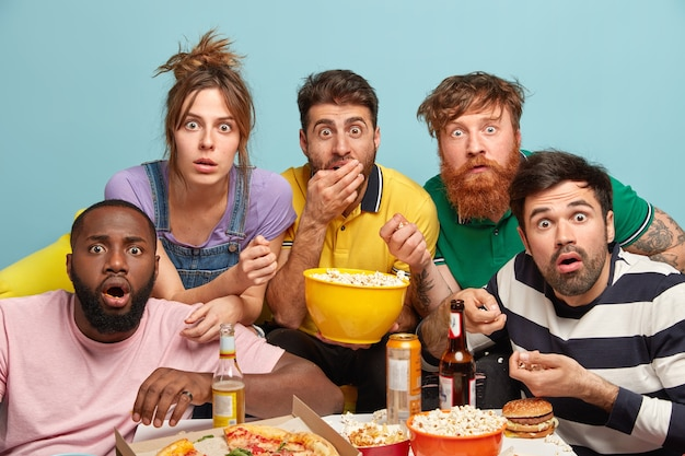 Photo of five mixed race woman and men watch thriller movie, horrible news, look in panic, eat popcorn, stare with bugged eyes, isolated over blue wall, being scared. scary film at home