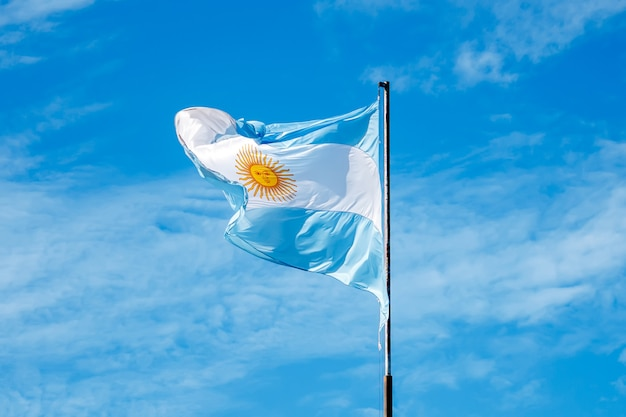 Photo of the flag of argentina against a blue sky with clouds
