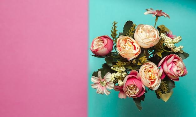 Photo of a flat lay bouquet of flowers roses on a pink and blue textured background with patterns