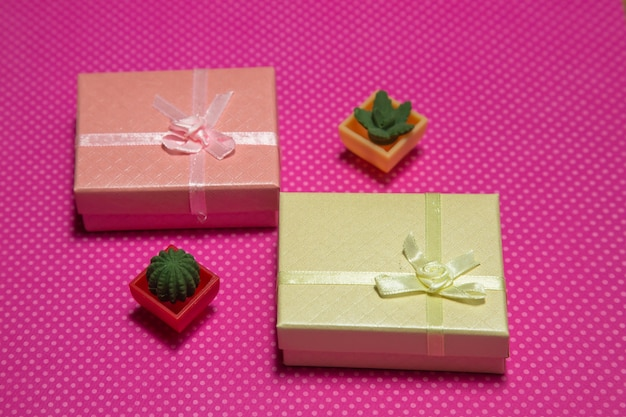 Photo flat lay of a gift boxes with a bow under points of view on a pink background front view high