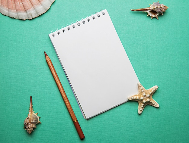 Photo flat lay layout of a blank sheet of paper in a notebook and a pencil