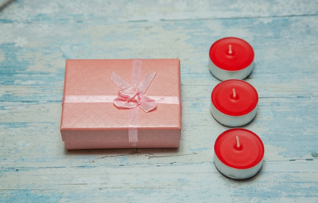 Photo flat lay a pink gift in the form of a pink box and candles on a blue background with patterns
