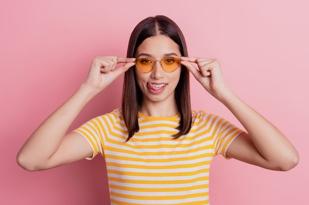 Photo of flirty carefree tourist lady fingers hold sunglass protrude tongue lick lip on pink background