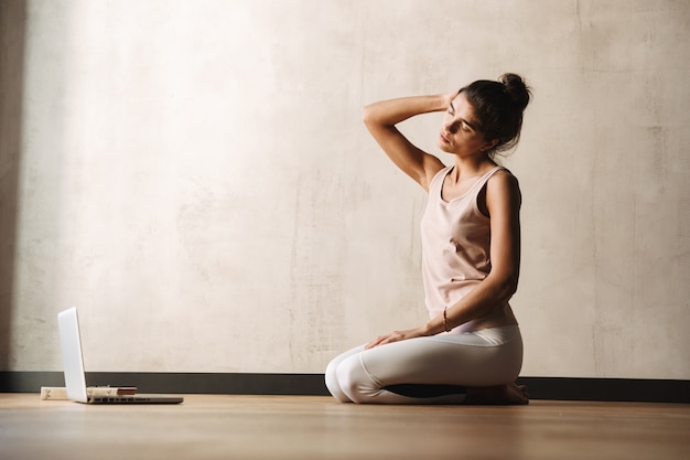Photo of focused young woman in sportswear doing exercises with closed eyes and using laptop while sitting on floor at home
