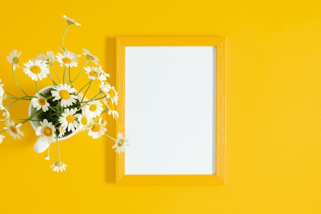 黄色いテーブルの上のフォトフレームとカモミールの花。フラットレイトップビュー