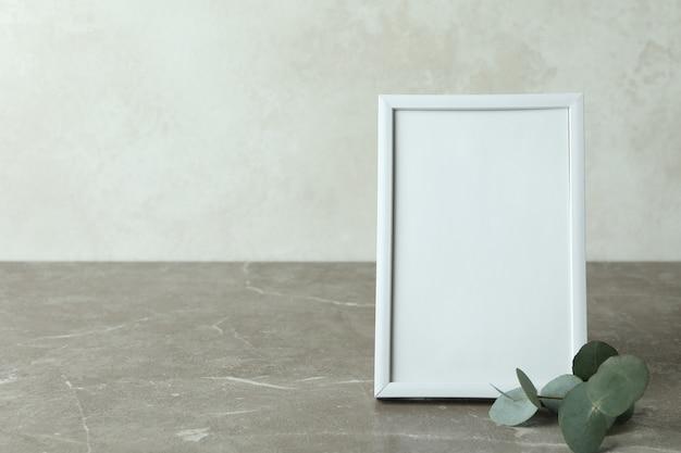 白いテクスチャ背景に対して灰色のテクスチャテーブル上のフォトフレームとユーカリの小枝