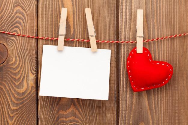 Рамка для фотографий и игрушечное сердечко ручной работы на деревянном фоне