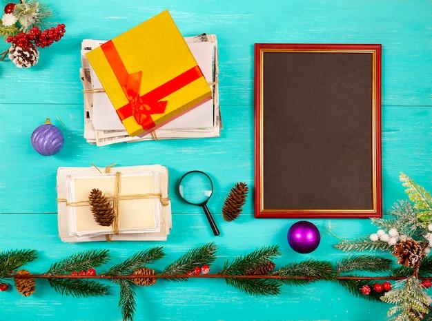 스택, 선물, 크리스마스 장식 및 푸른 나무 테이블에 크리스마스 트리, 평면 누워 사진 프레임 및 오래된 사진