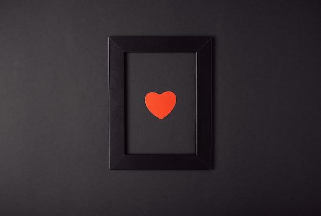暗い(黒)背景にフォトフレームと赤いハート。バレンタインデーのコンセプト。フラットレイ、上面図。