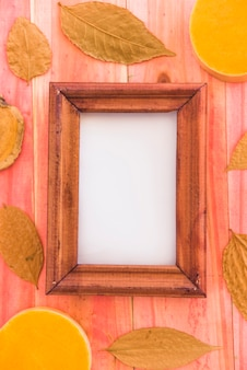 Photo frame between dry foliage and fruits