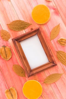 Photo frame between dry leaves and fruits