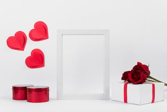 Photo frame between present with flowers, paper hearts and boxes