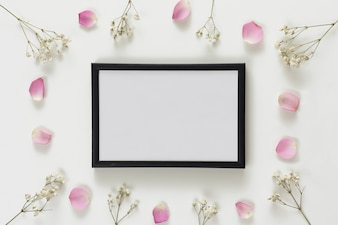 Photo frame between set of fresh rose petals and plant twigs