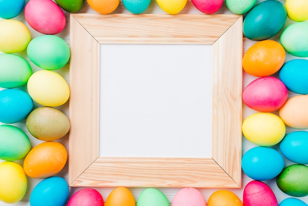 Photo frame between bright collection of easter eggs