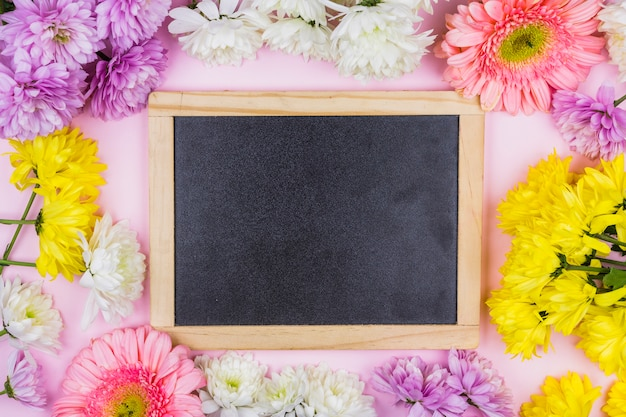 Photo frame between bright fresh flowers