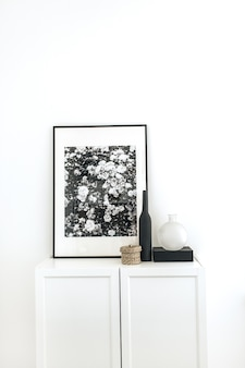 Photo frame on chest of drawers with decoration at white wall