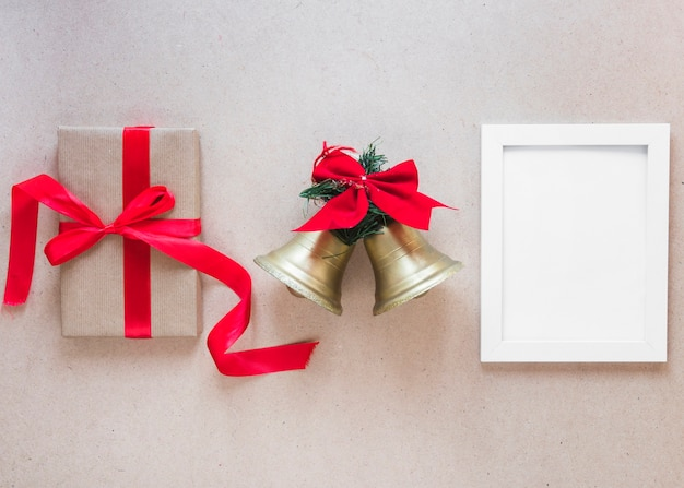 Photo frame between christmas bells and gift box