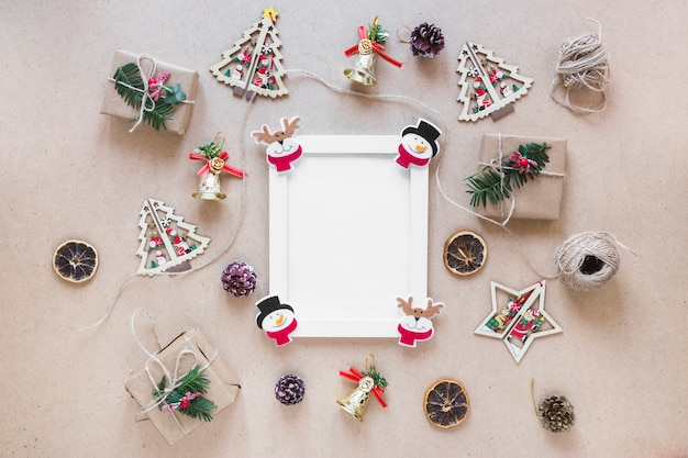 Photo frame between christmas decorations and gift boxes
